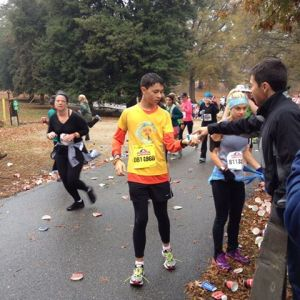 Alex Gaura stopping for water and snacks at mile marker 7 of the Richmond Half Marathon in 2013